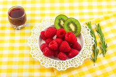 Fresh Red Raspberries on a white artistic plate. Red Fresh Raspberries on a white artistic plate with cookies, rosemary, chocolate and cream in the background Stock Photography