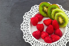 Fresh Red Raspberries on a white artistic plate. Red Fresh Raspberries on a white artistic plate with cookies, rosemary, chocolate and cream in the background Royalty Free Stock Photography