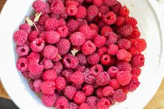 Fresh red raspberry in white bucket bright stock photos