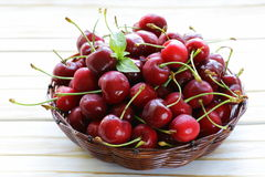 Fresh red ripe cherries in wicker basket Royalty Free Stock Photo