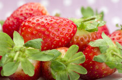 Fresh red ripe strawberries on a plate. Pink dotted background. Stock Photo