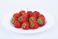 Fresh red ripe strawberries on a white plate Royalty Free Stock Photo