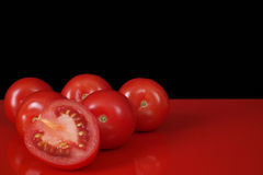 Fresh red Roma tomatoes on red table and black background, copy Stock Image