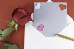 A fresh red rose big bud and petals with green leaves near white triangle envelope and empty silver letter stock photo