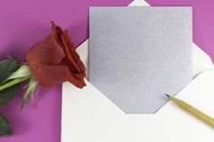 A fresh red rose big bud and petals with green leaves near white triangle envelope and empty silver letter wooden pencil stock photo