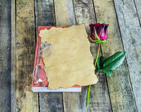Fresh red rose,glasses and old paper on notebook on a wooden bac Royalty Free Stock Photography