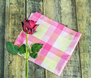 Fresh red rose and napkin on a wooden background. Stock Photography