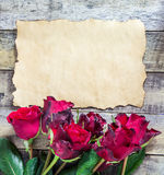 Fresh red rose and old paper on wooden background Royalty Free Stock Photography