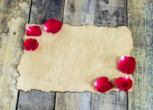 Fresh red rose and old paper on wooden background Stock Images