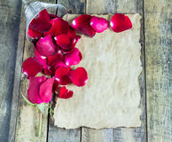 Fresh red rose and old paper on a wooden background Stock Image