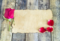 Fresh red rose and old paper on a wooden background. Stock Images