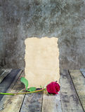 Fresh red rose and old paper on wooden background Stock Photography