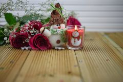 Romantic christmas winter season photography image with red roses and a lit candle with snowman decoration. Fresh red roses flowers with glitter petals laid on a Royalty Free Stock Image