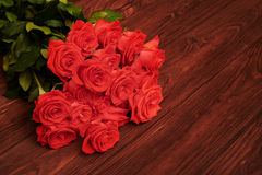 Fresh red roses over brown background Stock Images