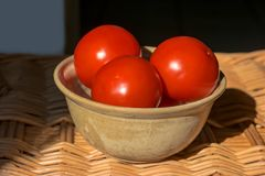 Fresh red round tomatoes in a bowl on the woven table. Close-up of fresh red round tomatoes in a bowl on the woven table Royalty Free Stock Photography