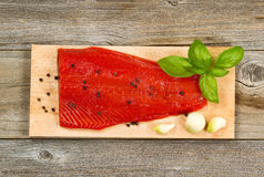 Fresh red salmon fillet on cedar cooking plank with spices and h. Top view shot of fresh red salmon fillet on cedar cooking board with peppercorn, garlic and Stock Photos