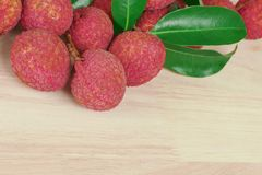 Fresh red skin lychee with leaves on wooden background with copy space royalty free stock images