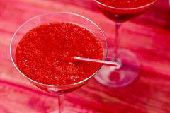 Fresh red smoothies. Closeup of some cocktail glasses with fresh red smoothies on a red wooden surface Royalty Free Stock Photos