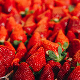 Fresh red strawberries arranged in baskets at marketplace Stock Photos