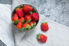 Fresh red strawberries in bowl with napkin. Summertime concept, berries top view concept royalty free stock photo