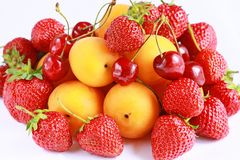 Fresh red strawberries, cherry and apricots. On white royalty free stock photos