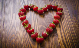 Fresh red strawberries lying in heart form. Top view. Stock Photo