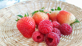 Fresh red strawberries and raspberries. In basket stock photo
