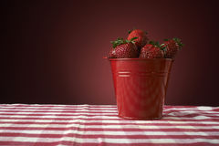 Fresh red strawberries in a red bowl on checkered tablecloth Royalty Free Stock Photos