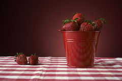 Fresh red strawberries in a red bowl on checkered tablecloth Stock Image