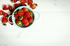 Red strawberries in colander on a white wooden table. Fresh red strawberries in a small colander on a white wooden table Royalty Free Stock Image
