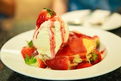 Fresh red strawberries topping vanilla ice cream on pancake seasoned with strawberry sauce. Healthy sweet dessert, Food royalty free stock images