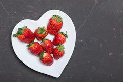Fresh red strawberries on white heart shaped plate on black tabletop Royalty Free Stock Photos