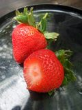 Fresh red strawberry and green leaf on black plate Royalty Free Stock Photo