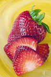 Fresh red strawberry and slices. Beautiful red fresh strawberries on colorful yellow swirl plate with one berry sliced Royalty Free Stock Image