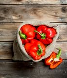 Fresh red sweet pepper in the sack and a half of ripe pepper. On wooden background stock image