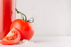Fresh red tomato drink and pulpy tomatoes with juicy piece, straw, salt on light soft white wood table, copy space, closeup. Fresh red tomato drink and pulpy Stock Photos