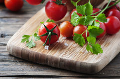 Fresh red tomato with green parsley Royalty Free Stock Images