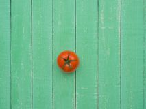 Red tomato on a wooden table. Fresh red tomato lies on a wooden table Royalty Free Stock Photo