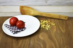 Fresh red tomato oats kitchen cloth spoon wooden surface rustic food breakfast healthy organic Royalty Free Stock Photos