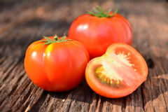 Fresh red tomato on old brown wood table at the morning Royalty Free Stock Photo