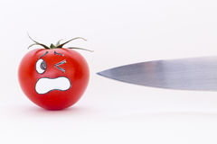 Fresh red tomato with scared face and sharp knife blade Stock Image