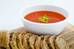 Fresh tomato soup with small bread and basil leaf on a plate with paper textured background Royalty Free Stock Photography