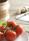 Fresh red tomatoes. Some lettuce, wooden tub, knife, cloth and some garlic stock photography