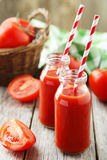 Fresh red tomatoes in basket and juice in bottles on the grey wooden background Stock Images