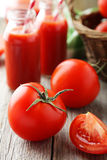 Fresh red tomatoes in basket and juice in bottles on the grey wooden background Royalty Free Stock Images