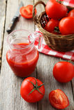Fresh red tomatoes in basket and juice in jug on a grey wooden background Stock Image