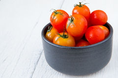 Fresh red tomatoes in black bowl on white wooden table Stock Image