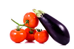 Fresh red tomatoes on bunch and eggplant. On white background Royalty Free Stock Photo