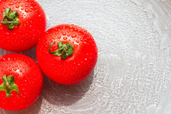 Fresh red tomatoes with drops on a plate. For eating Stock Images