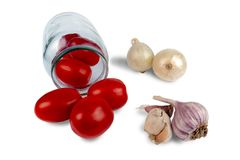 Fresh red tomatoes in a glass jar next to the onion and garlic are all on a white background.  stock images